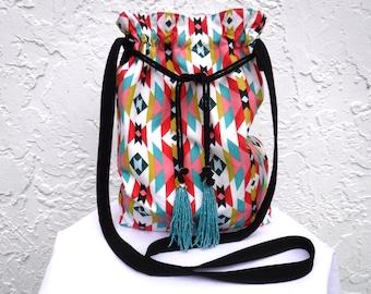 Southwestern print drawstring crossbody bag. Purse with geometric/Aztec print has turquoise beaded tassels. Show off your desert boho style.