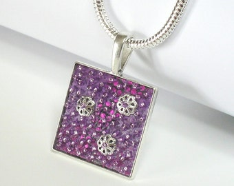 """ART PENDANT: """"inchworm"""""""" Lavishly embroidered art piece necklace with applique, beads and sterling silver chain.  Handmade."""