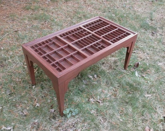 Cherry wood coffee table with a printers type box top in which you can display collections by lifting out the fitted glass top.