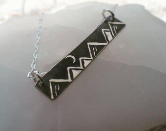 Silver horizontal mountain scene necklace.