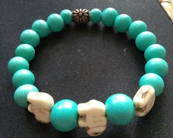Three elephants and turqouise wood beads bring this bracelet it's simple style