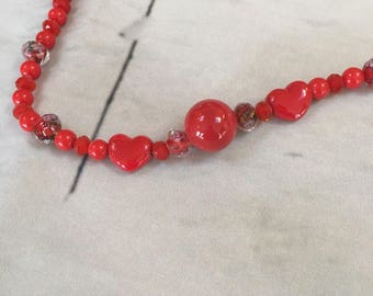 Red ceramic beads combined with red multi beads hand strung on bead wire with easy clasp hook.