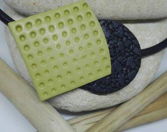 Colgante hecho a mano de arcilla polimérica con piezas superpuestas texturizadas combinando 2 colores
