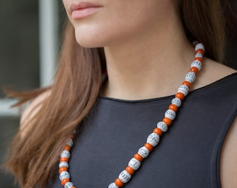 A bold and striking, orange and white necklace, made from paper beads and wooden beads.