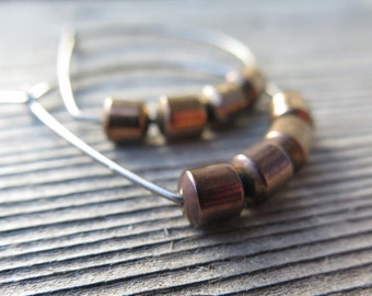hypoallergenic niobium wire hoops with copper hematite beads. hammered silver hoop earrings. copper and silver jewelry.