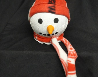 A adorable light up snow person with a fleece Detroit Red Wings hat and scarf