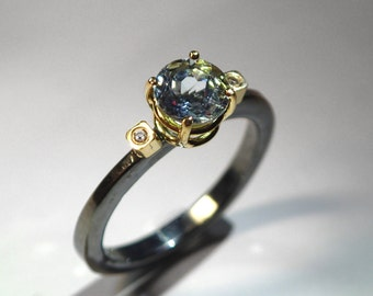 A luxurious oxidized silver solitaire ring with aquamarine and diamonds. An expensive engagement ring with high quality gemstones.