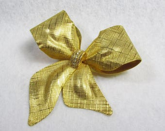 Large gold toned etched metal rhinestone ribbon bow brooch.
