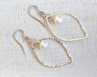 Drop pearl earrings with silver surround leaf design