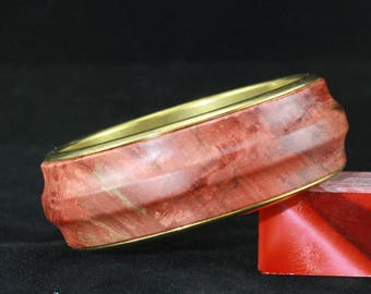 Hand turned wood bracelet made with red dyed and stabilized maple burl with brass sleeves.