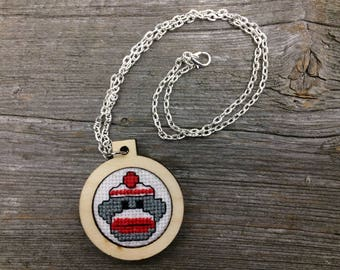 Cross stitch sock monkey necklace pendant in laser cut wood frame on silver tone chain by Canadian Stitchery