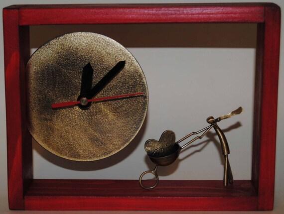 Desk bronze clock with dark red wooden frame.