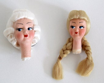 Vintage handmade fabric doll heads with painted faces and intricate hair-dos