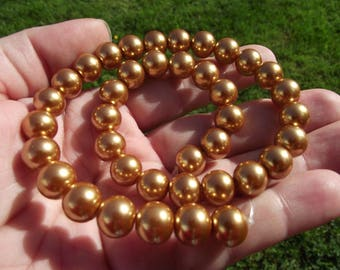 4 gold 10 MM round shell beads.