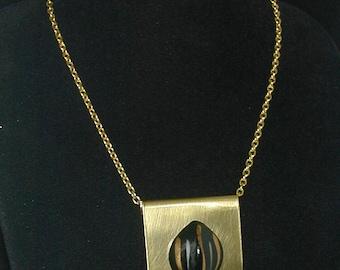 Black lucite cabochon on brass shield pendant.
