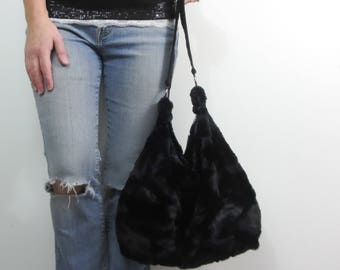 black faux fur bucket bag lined in purple. over the shoulder purse with two large accent rings. ready to ship and clearance priced.