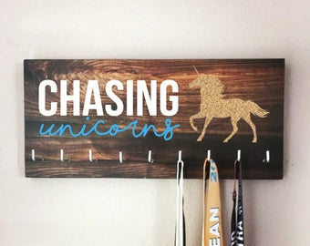 """Race Medal Holder - """"CHASING unicorns"""" white and blue with wood grain background - 16"""" wide"""