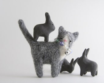 Gray cat with white face and a necklace, brooch