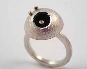 A crater of the moon. A modern silver and gold ring with a small diamond and two studded gold granules.