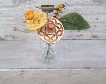 tan, yellow, and pale green button flower bottle bouquet
