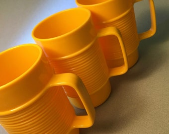 Set of three vintage Rubbermaid bright yellow plastic tumblers with handles