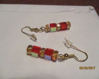 dangle earrings of red and gold crystal. Gold tone wires and fish hook ear wires.