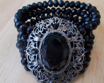 4 Row Black Crystal Beads Stretch Cuff Bracelet with a Silver Tone and Black Pendant