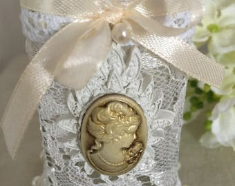 Very pretty bottle is square glass fully dressed with cotton lace and ruffles, pearls, and a cameo
