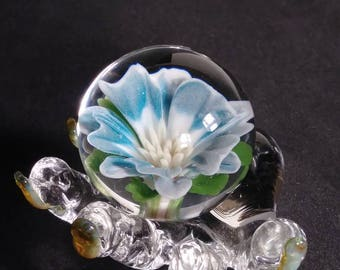 Blue and white flower marble held by a detailed display hand.