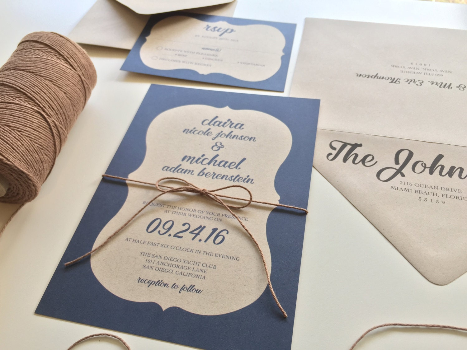 This rustic kraft paper wedding invitation has an ornate blue border and is tied sweetly with twine. The invitation is shown on 100% recycled kraft paper and co