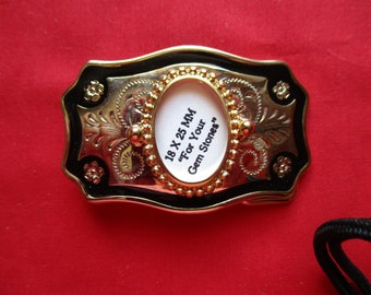 Gold Tone with black trim belt buckle to hold hold a 18 by 25 mm cabachon.