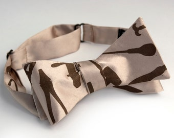 """Tool bow tie. Champagne fabric, self-tie. """"Weapons of Mass Construction."""" Chocolate brown print."""