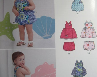 Simplicity/New Look 6385 -- Cute dress and jumper pattern in sizes Newborn to Large. Pattern is uncut and factory folded.
