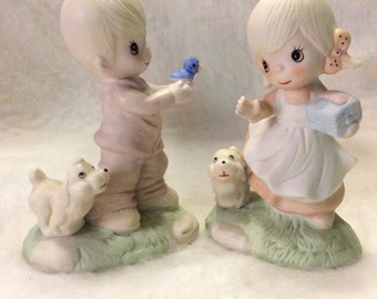 Vintage early precious moments design boy and girl with dogs figurines.