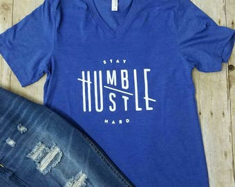 Stay humble. Hustle hard. Heathered royal vneck.  Graphic shirt. Soft shirt. Plus size. Available in small to 3x.