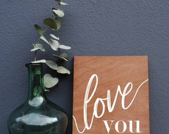"Wooden sign with the message ""love you"" for a country wedding"