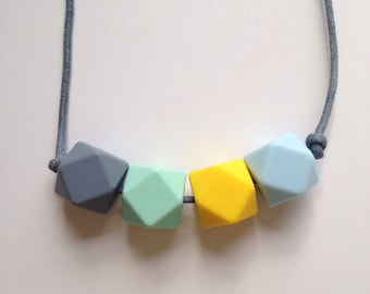 Teething necklace in grey, mint green, yellow and ice blue; made from BPA free chewable silicone hexagon beads by Little Gnashers