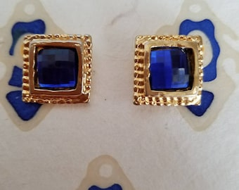Dramatic square gold tone post earrings with bright blue rhinestones.