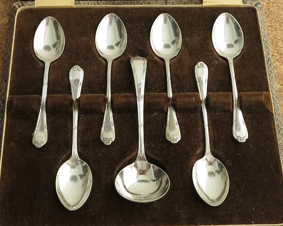 Antique silver plated cutlery in presentation box, 6 teaspoons and cream ladle, grooved handles with bows at the ends, Edwardian