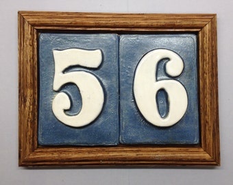 Address tiles in Oak frame plaque, multiple color choices available. PVc weatherproof backplate and concealed mounting.