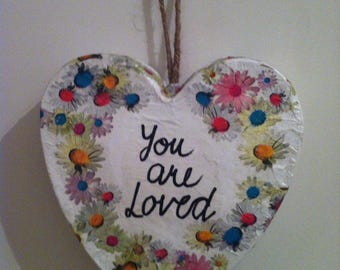 "Paper mache heart decorated ""you are loved"" with flowers."