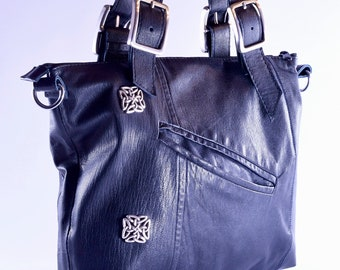 Black upcycled tote bag from repurposed leather with large buckle accents.