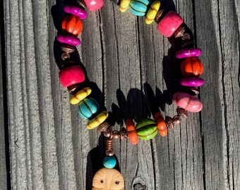 Multi colored, various shaped & size, semi-precious stone, copper/silver bracelet on a stretch band with a carved bone owl.