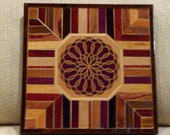 Wood wall art sculpture featuring a digitalwood.com inlay kit surrounded by a variety of exotic wood pieces.