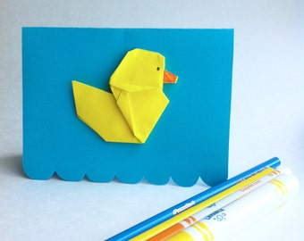 Greeting card - Yellow duckling origami card on a cyan blue background. Perfect for a baby shower or birthday, duck in a bath or water waves