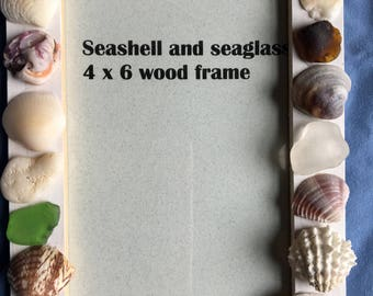White 4x6 wood frame with seashells and sea glass