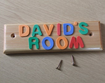 Wooden door name plate for children's or baby's bedroom door or playroom. Letters are foam and brightly coloured.