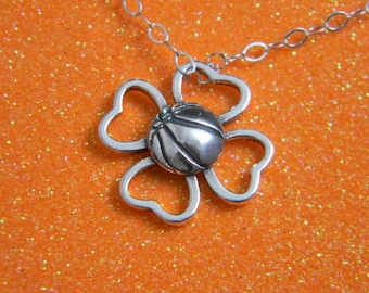 "Basketball nestled in 4 leaf clover with 18"" silver chain"