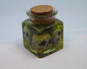 Green glow-in-the-dark Bottle o' Skulls, mixed-media sculpture