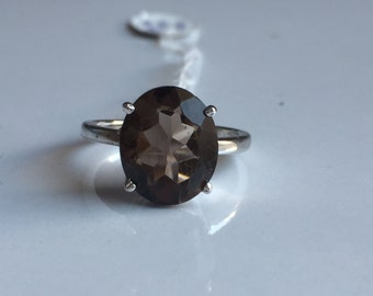 A beautiful ring is made in 925 sterling silver with full cut facetted  smoky stone